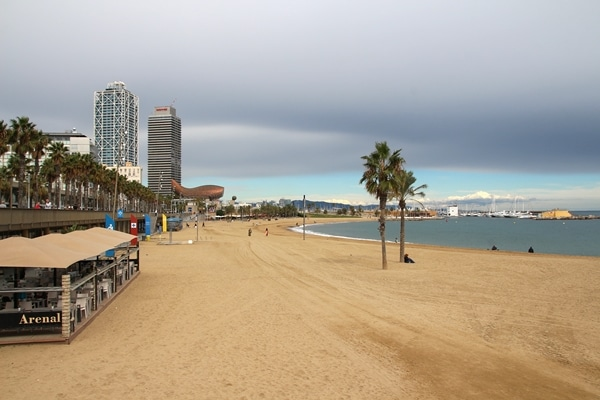 A sandy beach with buildings in the distance