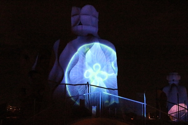 illumination of a jelly fish on the side of a stone chimney at night