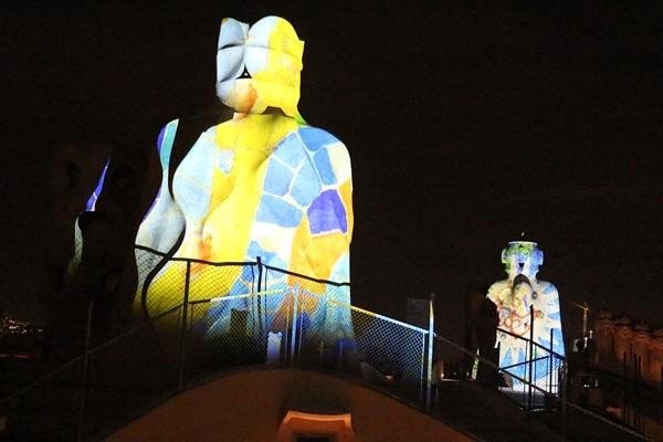 stone chimneys illuminated with colorful images at night