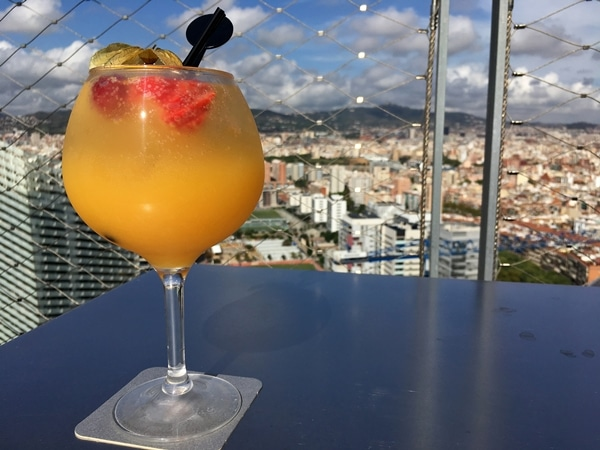 A glass of white sangria overlooking Barcelona from a rooftop