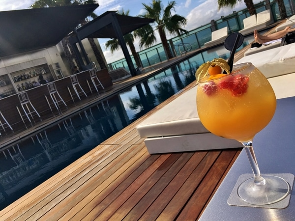 A glass of a fruity cocktail next to a pool with palm trees