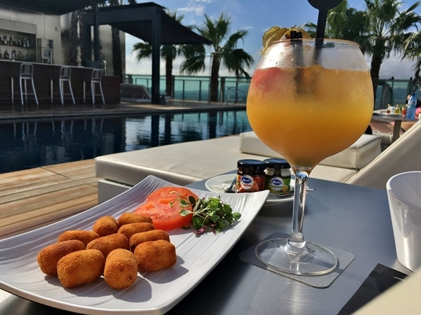 A plate of food and a glass of sangria on a poolside table