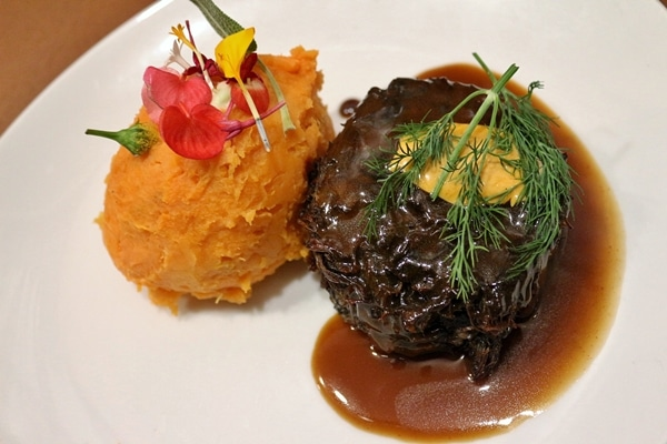 braised beef cheeks and mashed sweet potato on a white plate