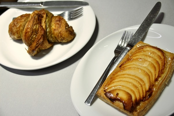 a croissant and apple tart on white plates