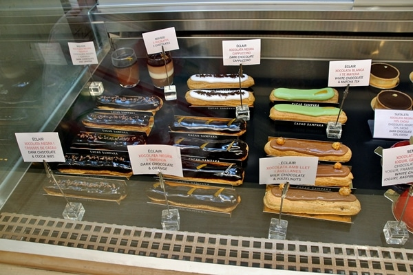 a variety of eclairs in a pastry display case