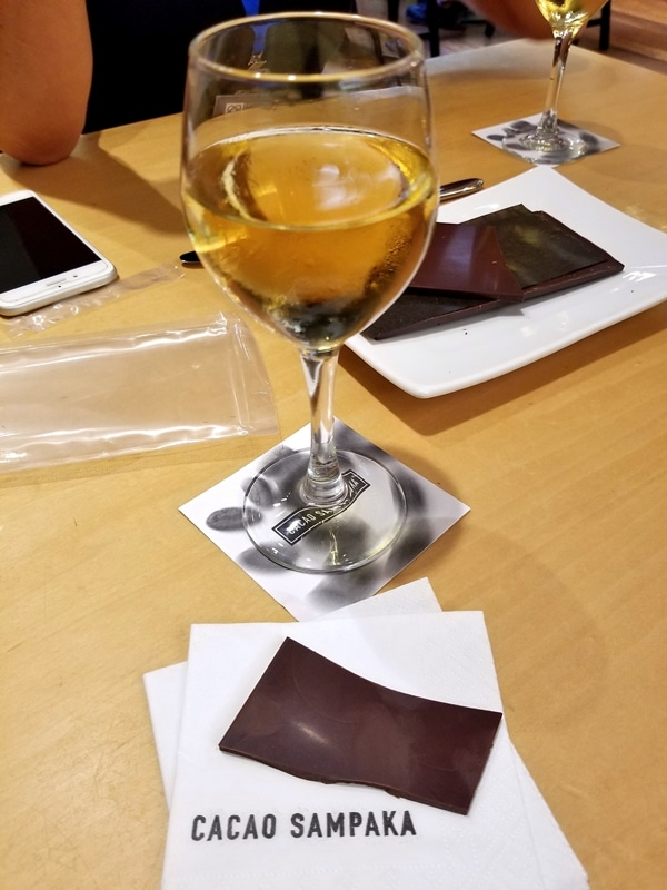 A glass of wine and a bar of chocolate on a wooden table