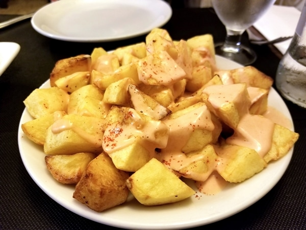 a plate of fried cubed potatoes topped with pink sauce