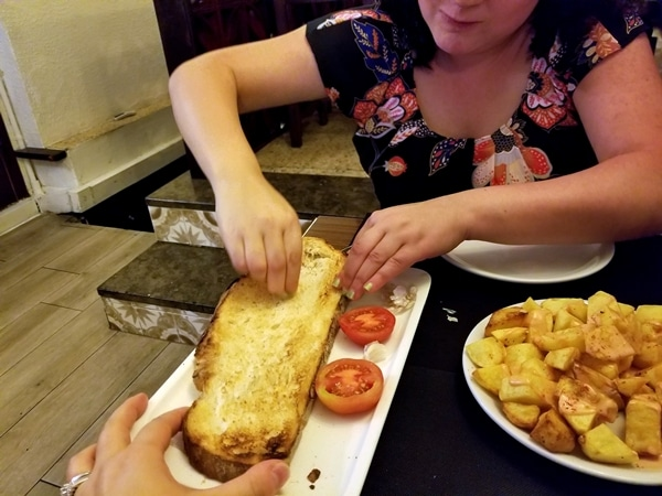 A woman rubbing a piece of garlic on a slice of toasted bread