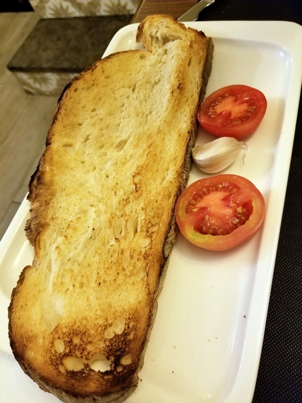 a giant piece of toasted bread with a halved tomato and garlic clove on the side