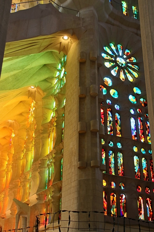 a kaleidoscope of colorful light streaming through stained glass windows inside Sagrada Familia