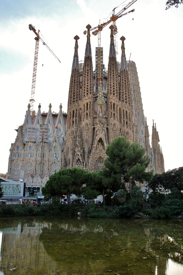 a wide view of Sagrada Familia from across a pond