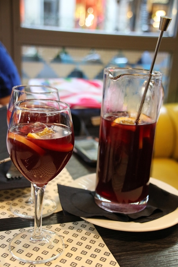 2 glasses of red sangria next to a pitcher of sangria