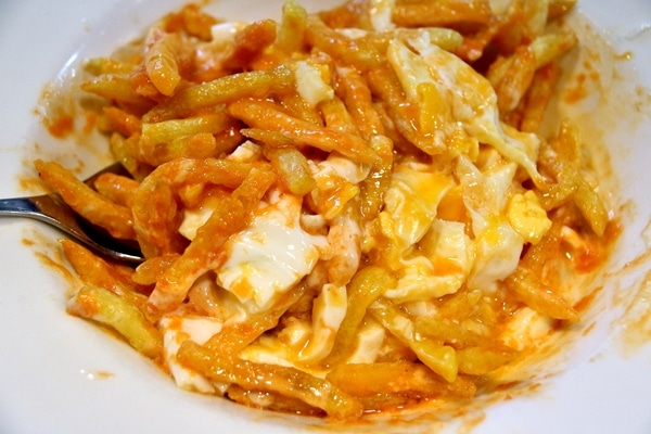 a mixture of french fries with cut up egg and sauce in a white dish
