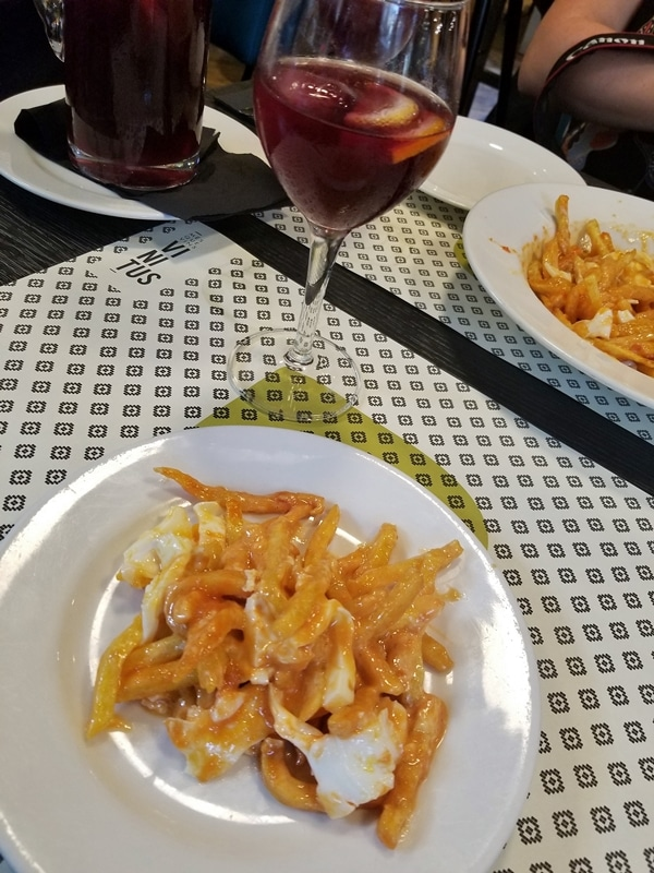 a plate of food and a glass of sangria on a table