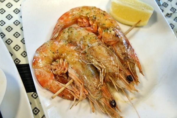 closeup of grilled langoustines on a white plate