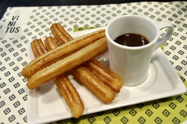 a plate of fried churros with dipping chocolate