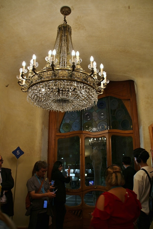 A group of people standing in a room under a chandelier