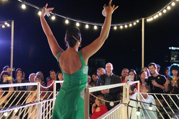 a female flamenco dancer in a green dress outdoors at night