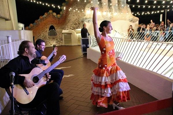 2 guitarists and a female flamenco dancer in an orange dress
