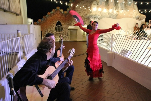 A group of people playing the guitar next to a flamenco dancer wearing red