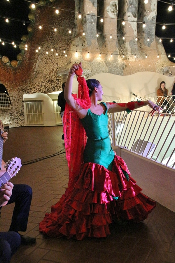 a flamenco dancer wearing a green and red dress