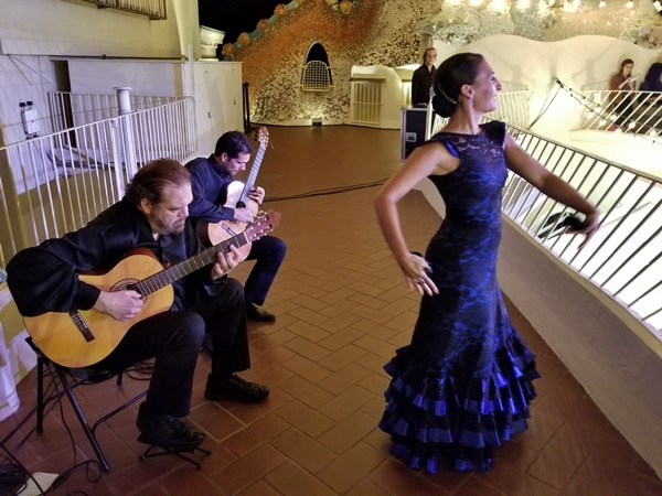 two flamenco guitarists and a dancer wearing blue