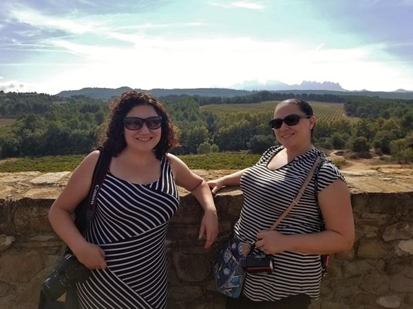 2 women posing in front of a vineyard