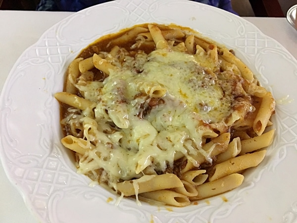 A dish is of pasta covered with melted cheese