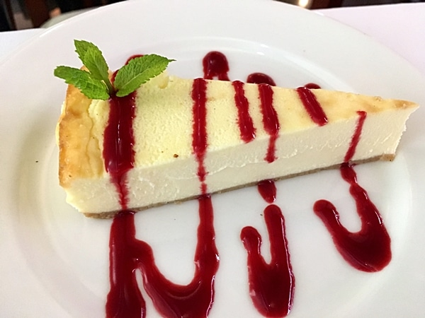A piece of cheesecake topped with red sauce