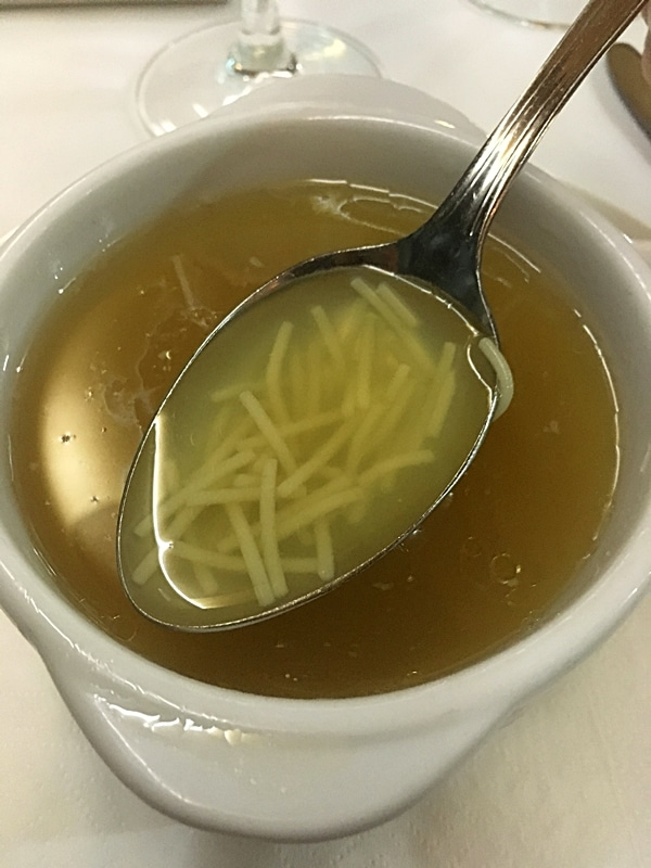 A bowl of noodle soup and a spoon