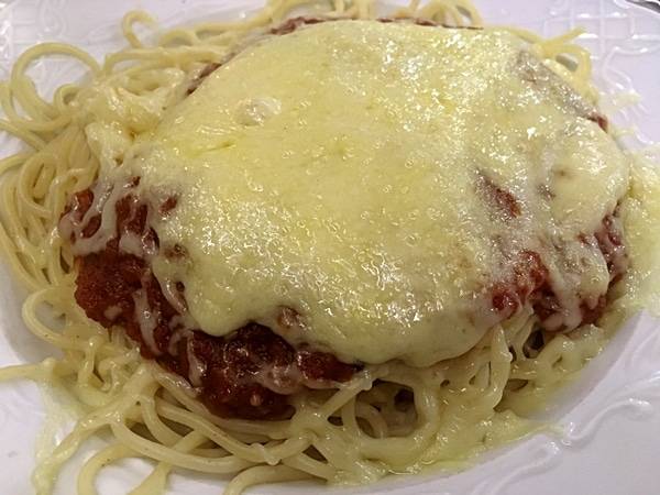 A close up of a plate of pasta with sauce and cheese