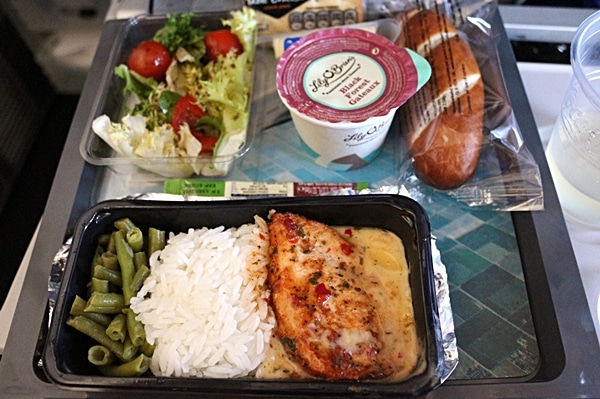 a tray of airplane food featuring chicken with rice and salad