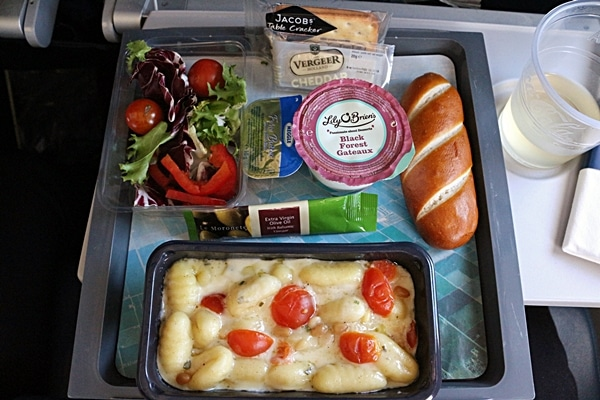 a tray of airplane food featuring gnocchi in a cream sauce with cherry tomatoes