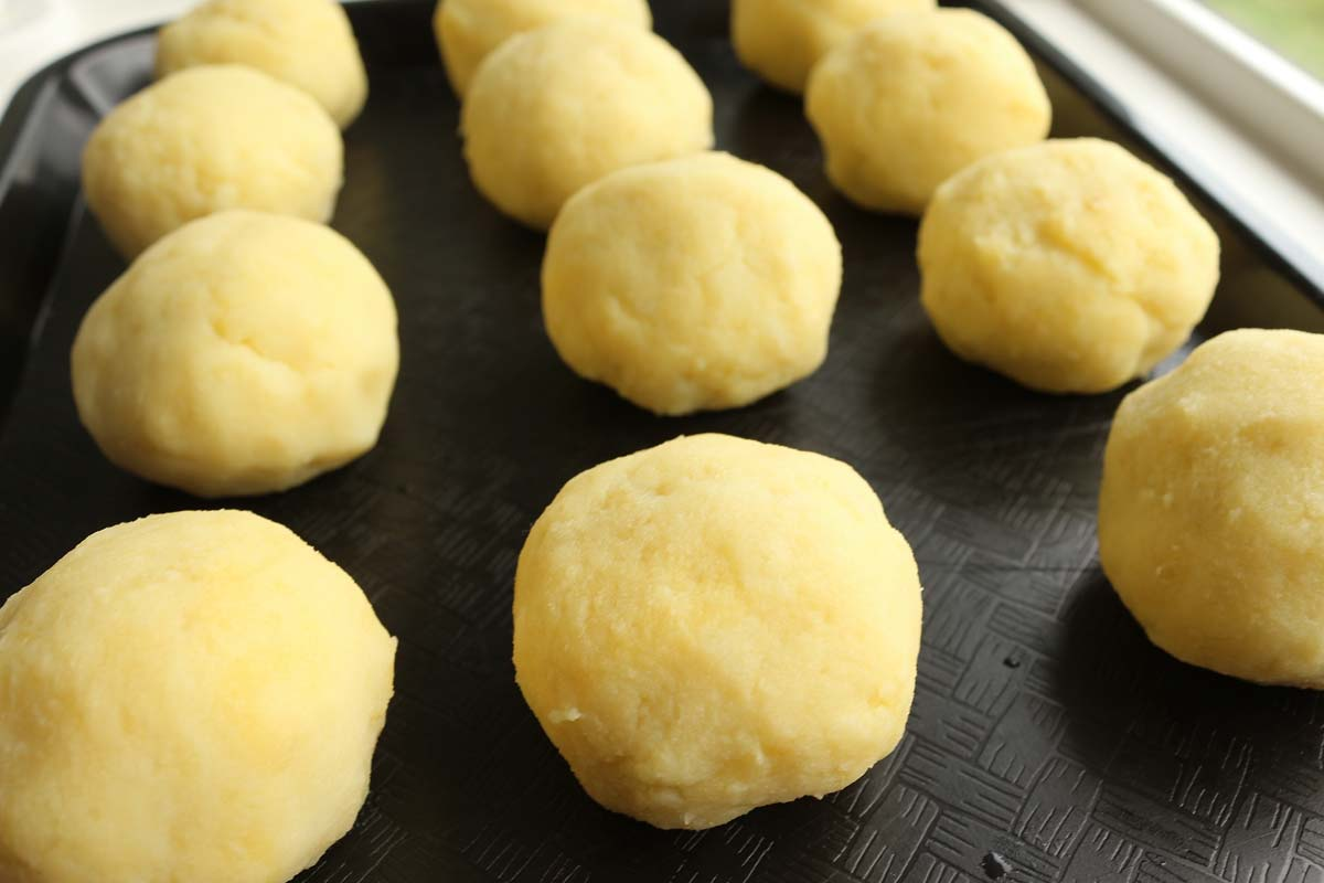 Mashed potato balls arranged in rows on a black tray.