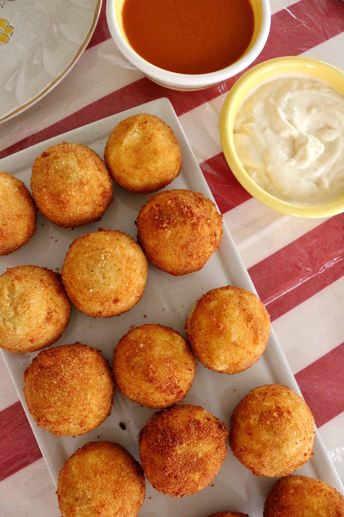 A white platter of fried potato bombas with bowls of red and white sauces.