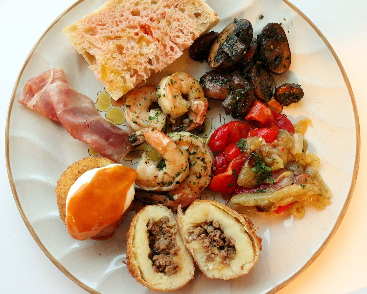 A plate of tapas including pan con tomate, mushrooms, shrimp, roasted vegetables, ham, and potato balls.
