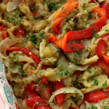 Closeup of roasted red peppers, eggplants, and onions with parsley in a colorful square dish.