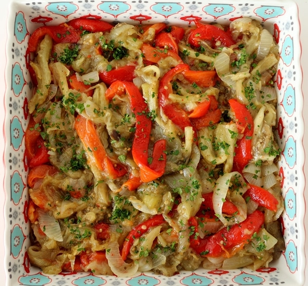 Roasted red peppers, eggplants, and onions with parsley, served in a decorative square dish