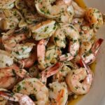A platter of garlic shrimp with parsley