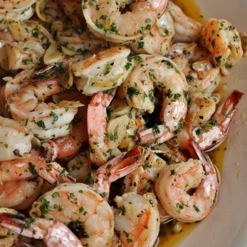 A platter of shrimp with sliced garlic and chopped parsley