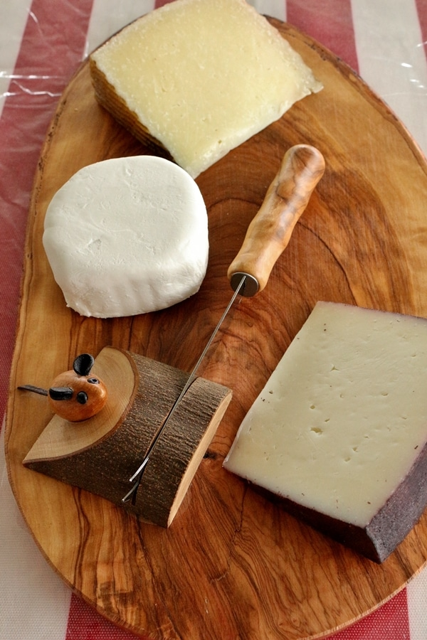 A wooden cheeseboard with a little wooden mouse figure on it, and 3 different cheeses.