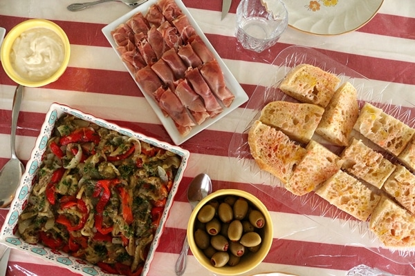 Serrano ham, roasted vegetables, olives, and bread on a red and white striped tablecloth covered table.