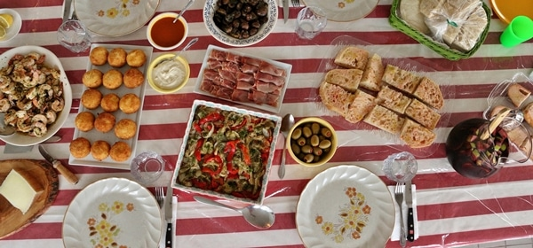 A table set with plates of various tapas. The tablecloth is red and white stripes, and the dishes include shrimp, potato balls, roasted vegetables, bread, and olives.