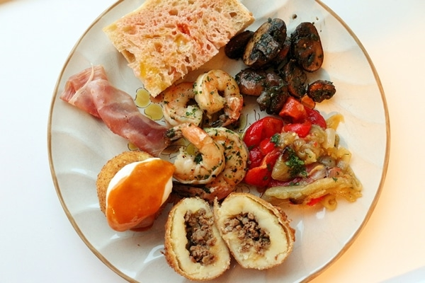 A plate of various Spanish tapas including garlic shrimp, sauteed mushrooms, escalivada, bombas, ham, and pan con tomate
