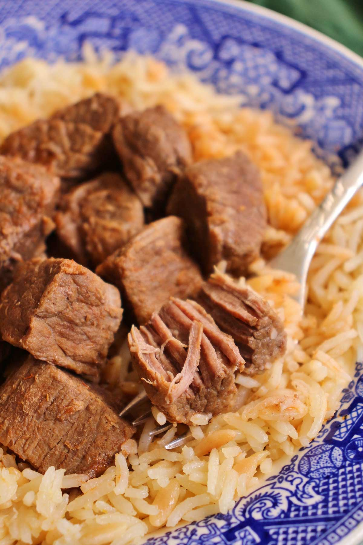 Closeup of a forkful of tas kabab stewed beef sitting in a bowl of rice pilaf.