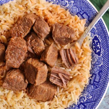 Cubes of stewed beef on top of rice pilaf in a shallow blue and white bowl.