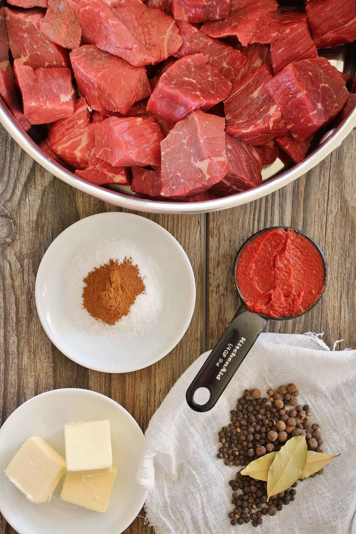 Cubes of raw beef in a pot, tomato paste, butter, and spices.