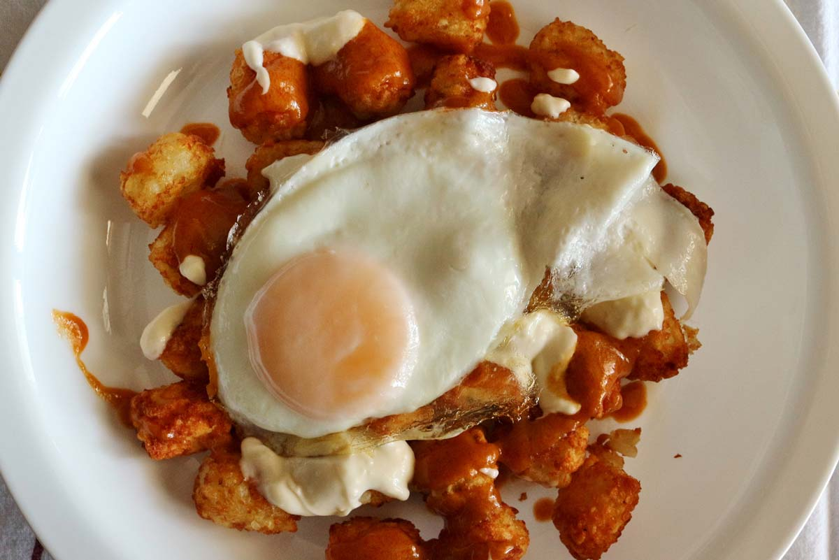 A white plate of tater tots topped with red and white sauces, and a fried egg.
