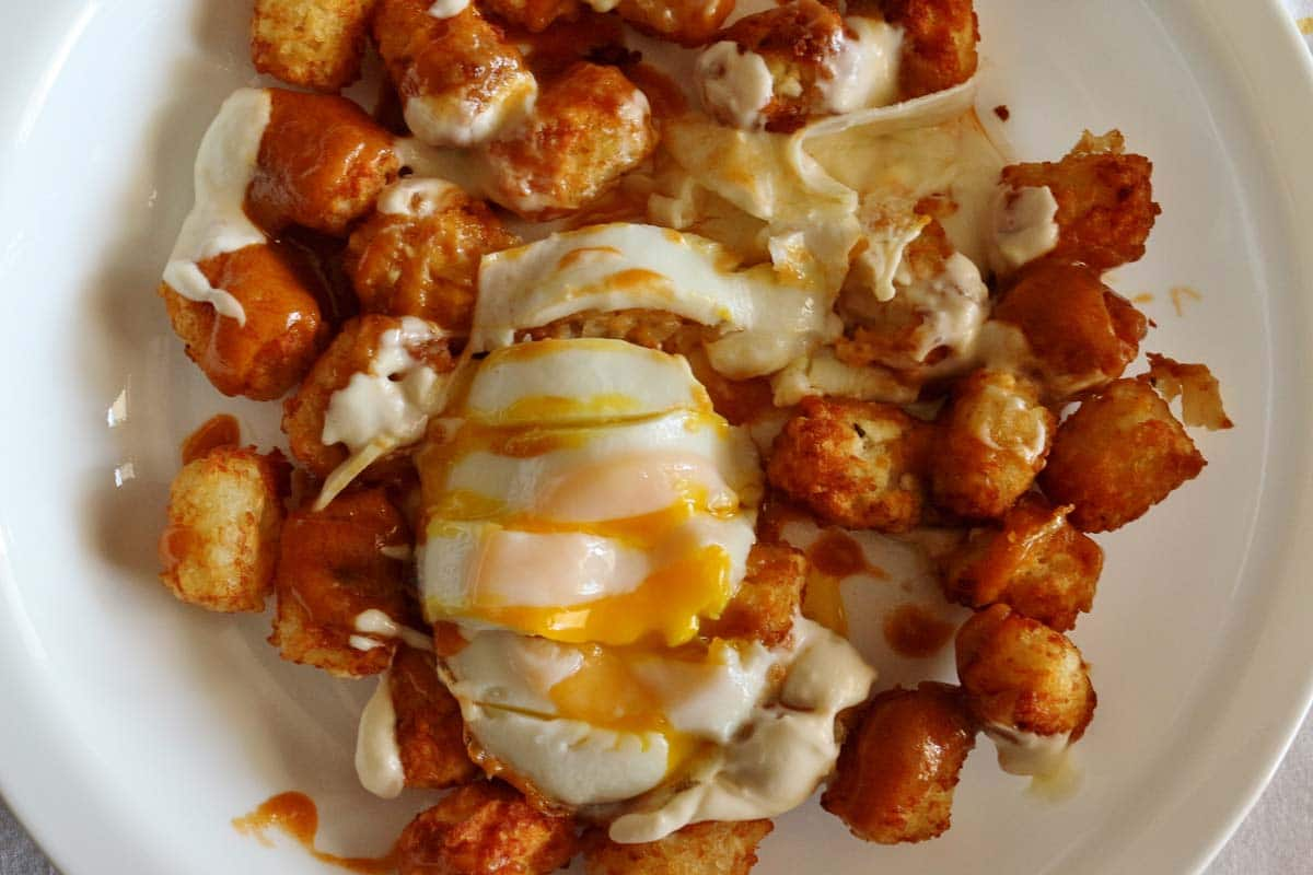 Tater tots topped with red and white sauces, and a sliced fried egg.