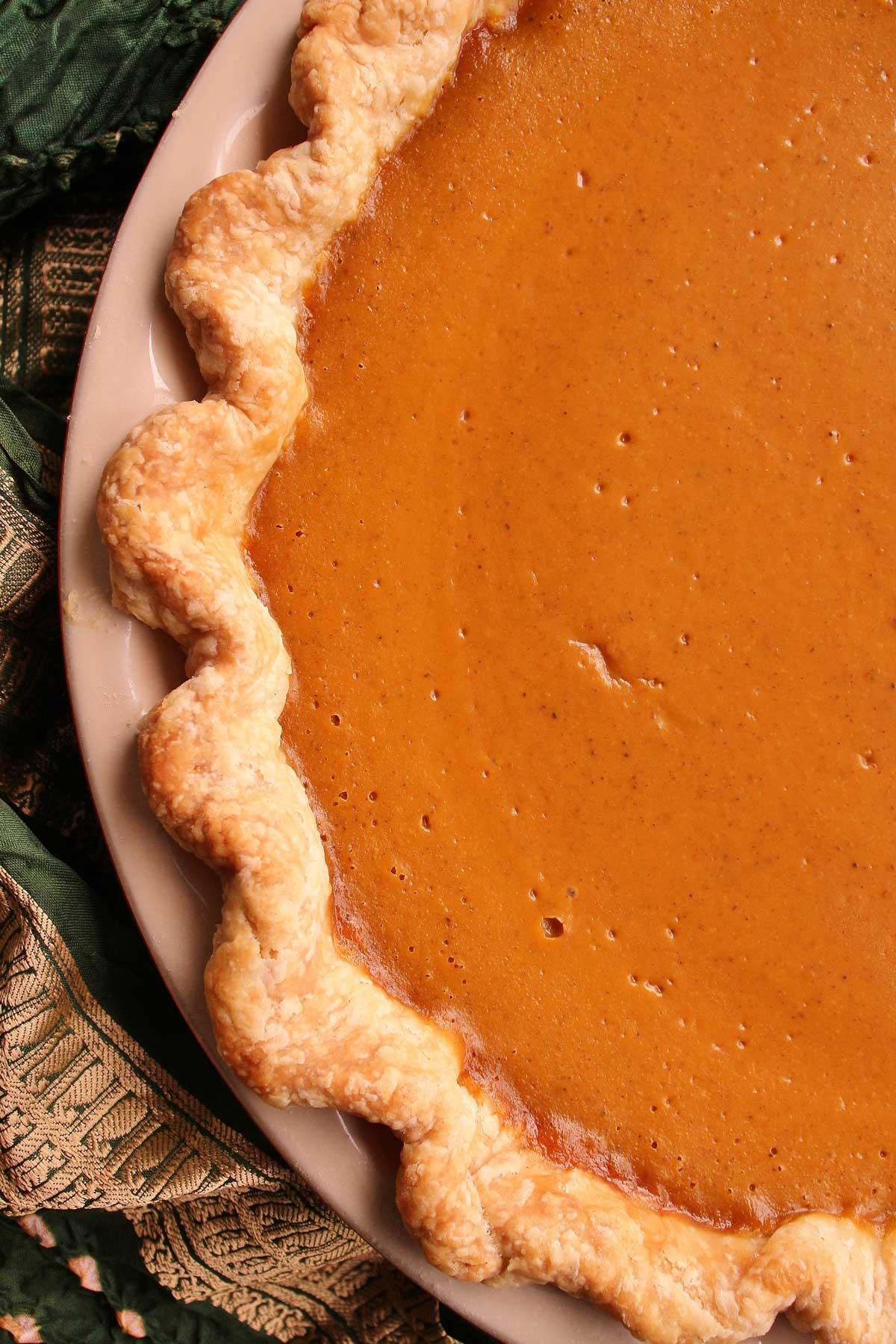 Closeup of one edge of a pumpkin pie with crimped edge in a ceramic pie dish.
